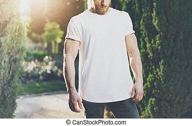 Photo Bearded Muscular Man Wearing White Blank t-shirt. Green Park Background and Sunlight effect. Horizontal Mockup