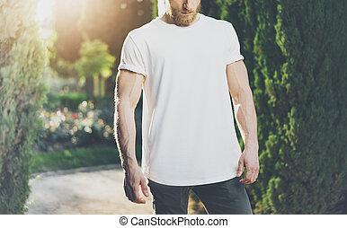 Photo Bearded Muscular Man Wearing White Blank t-shirt. Green Park Background and Sunlight effect. Horizontal Mockup
