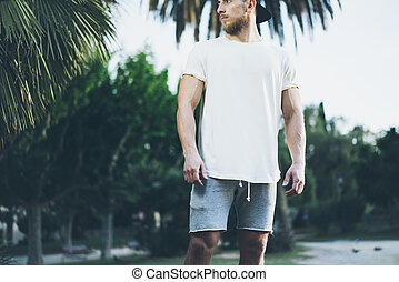 Photo Bearded Muscular Man Wearing White Blank t-shirt in summer time. Green City Garden.Relaxing time after hard work day. Blurred Background.Front view.Horizontal Mockup.