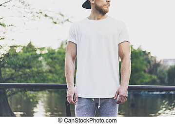 Photo Bearded Muscular Man Wearing White Empty t-shirt, snapback cap and shorts in summer holiday. Chilling time near the lake. Green City Garden Park Sunset Background. Front view. Horizontal Mockup