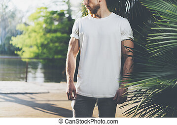 Photo Bearded Muscular Man Wearing White Blank t-shirt in summer time. Green City Garden, lake and palms Background,blurred. Horizontal Mockup
