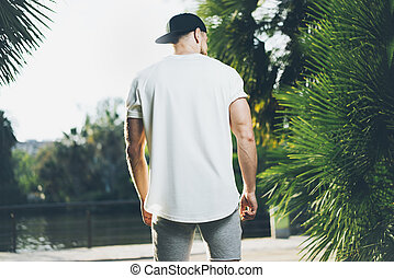 Photo Bearded Muscular Man Wearing White Blank t-shirt, snapback cap and shorts in summer time. Green City Garden Park Background. Back view. Horizontal Mockup