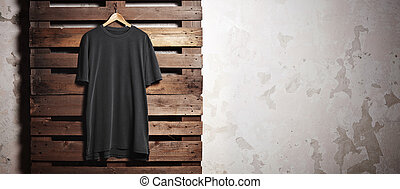 Photo black tshirt hanging in front of concrete wall. Wide...