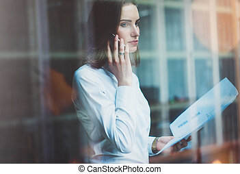 Photo business woman wearing white shirt, talking smartphone and holding documents in hands. Open space loft office. Panoramic windows background. Horizontal mockup, film effect