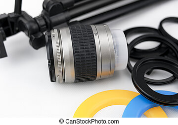 Photo camera lens close-up, with lens protectors and small tripod on white background