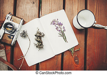 photo camera, mug, glasses, notebook and wildflowers herbs on wooden background, top view. stylish traveler hipster set flat lay. travel and wanderlust concept