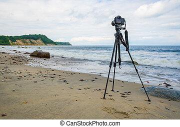Photo camera on seashore on stormy day