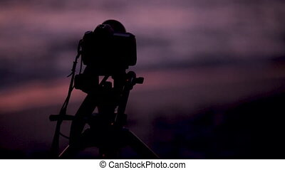 Photo camera taking pictures of sunset over the ocean -...