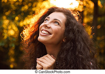 Photo closeup of brunette smiling girl 18-20 looking upward, while walking through park in sunny day with trees background