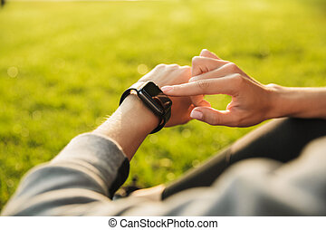Photo closeup of european woman 20s in sportswear, using smartwatch in green park on sunny day