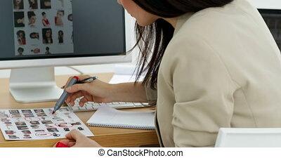Photo editor choosing photos and smiling at camera in...