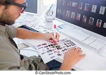 Photo editor marking the contact sheet at his desk in office