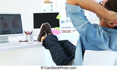 Photo editor relaxing at his desk in creative office