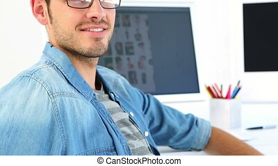 Photo editor smiling at his desk in creative office