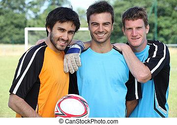 photo, football, trois, joueurs, poser, vêtements occasionnels