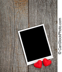 Photo frame and small red candy hearts on wooden background