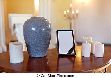 photo frame, cremation urn and candles in church - funeral...