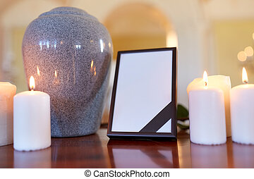 Photo frame, cremation urn and candles in church  Funeral