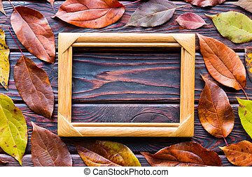 photo frame on a wooden background with autumn leaves