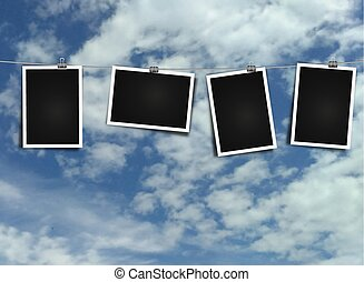 Photo frame on rope on sky background