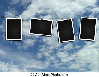 Photo frame on rope on sky background