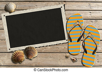 Aged photo frame with seashells on beach, flip flops sandals on wooden floor with sand