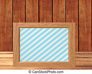 Photo frame on wooden table over wooden background