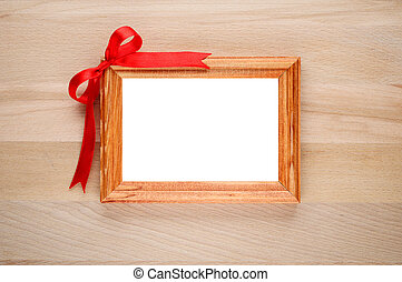 Photo frame with bow on wooden background
