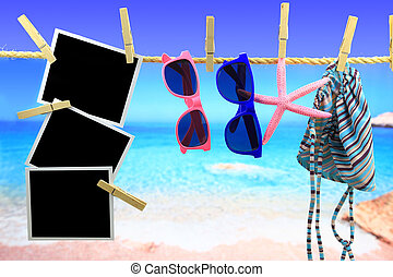 Photo frames and beach items hanging on a rope in front of the sea