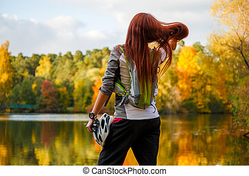 Photo from back of woman with backpack and bicycle helmet...