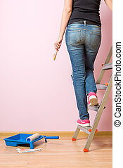 Photo from back of woman with brush standing on stepladder