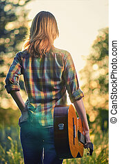Photo from the back of a female model with an acoustic guitar