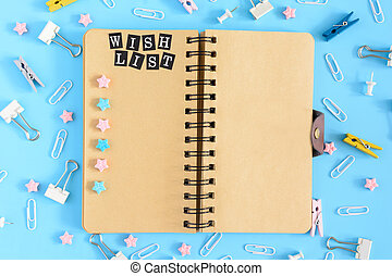 Photo from the top with scattered stationery. Open notebook on springs with brown leaves. A wish list. Clips, clerical buttons and asterisks in a mess on a blue background.