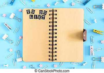 Photo from the top with scattered stationery. Open notebook on springs with brown leaves. The inscription To Do List. Clips, clerical buttons and asterisks in a mess on a blue background.