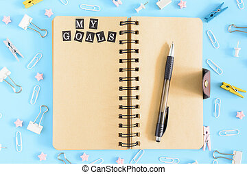 Photo from the top with scattered stationery. Open notebook on springs with brown leaves. The inscription My Goals. Clips, clerical buttons and asterisks in a mess on a blue background.