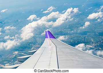 photo from the window of an airplane flying over Thailand, view of the wing