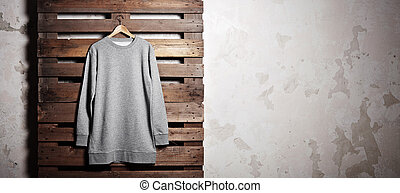 Photo grey hoody hanging in front of wood background - Photo...