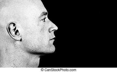 photo high contrast dark moody close up picture of a male head from side on black
