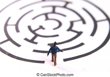 miniature figur toy young man walking into labyrinth, face the challenges to achieve goals