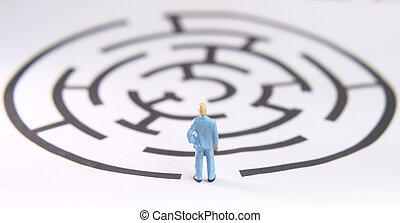miniature figure toy young man prepare to walk into labyrinth, face the challenges to achieve goals