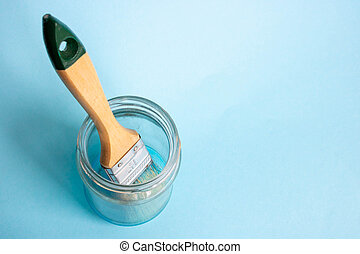 Photo of a painter's brush in a glass jar on a blue background