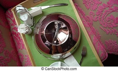 Photo of a silver serving dome cover and cup of tea or...