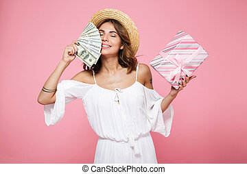 Photo of a young beautiful woman in straw hat, with closed eyes, holding dollar bills and gift box