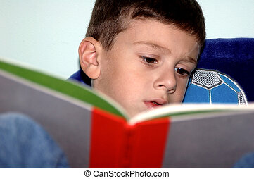 Boy Reading - Photo of a Young Boy Reading.  Some noise.