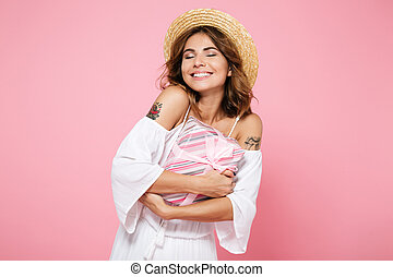 Photo of a young charming woman in straw hat, with closed eyes, hugging gift box