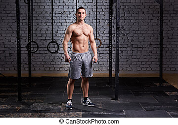 Photo of a young muscular crossfit sportsman while standing...