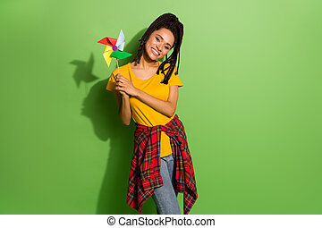 Photo of adorable pretty dark skin woman wear yellow t-shirt holding windmill toy isolated green color background.