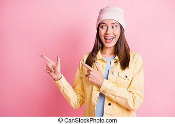 Photo of adorable shiny young lady wear casual outfit headwear looking pointing two fingers empty space isolated pink color background