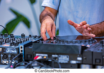Photo of adult dj working with his equipment. Close up shoot