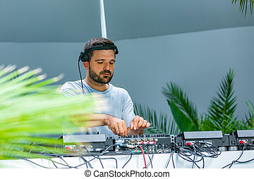 Photo of adult dj working with his equipment